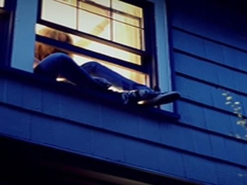 girl crawling out of window